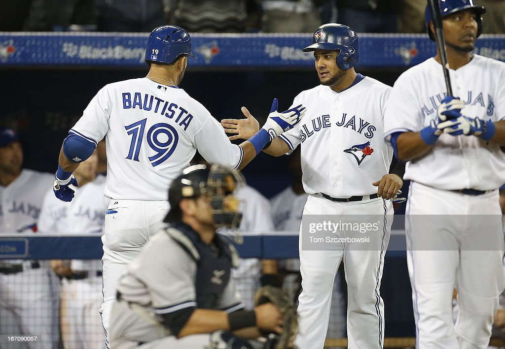 Jose Bautista #19 of the Toronto Blue Jays is congratulated by <a gi-track='captionPersonalityLinkClicked' href=/galleries/search?phrase=Melky+Cabrera&family=editorial&specificpeople=453444 ng-click='$event.stopPropagation()'>Melky Cabrera</a> #53 and <a gi-track='captionPersonalityLinkClicked' href=/galleries/search?phrase=Edwin+Encarnacion&family=editorial&specificpeople=598285 ng-click='$event.stopPropagation()'>Edwin Encarnacion</a> #10 after hitting a 2-run home run in the sixth inning during MLB game action as <a gi-track='captionPersonalityLinkClicked' href=/galleries/search?phrase=Francisco+Cervelli&family=editorial&specificpeople=4172506 ng-click='$event.stopPropagation()'>Francisco Cervelli</a> #29 of the New York Yankees watches on April 19, 2013 at Rogers Centre in Toronto, Ontario, Canada.