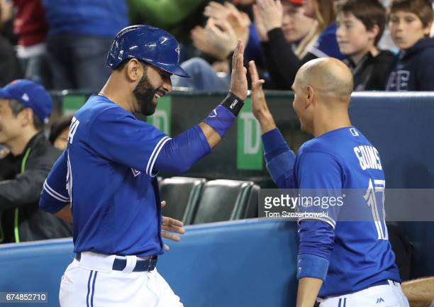 Jose Bautista of the Toronto Blue Jays is congratulated by Ryan Goins after scoring a run in the first inning during MLB game action against the...