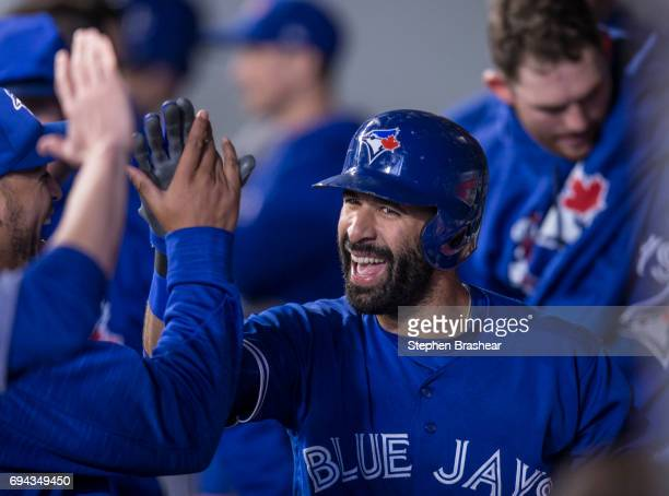 Jose Bautista of the Toronto Blue Jays is congratulated by teammates in the dugout after hitting a solo home run off of starting pitcher Sam Gaviglio...