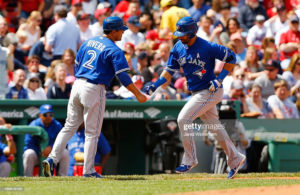 Jose Bautista #19 of the Toronto Blue Jays is congratulated by third base coach Luis Rivera #2 of the Toronto Blue Jays after hitting a solo home run in the third inning against the Boston Red Sox during the game on May 12, 2013 at Fenway Park in Boston, Massachusetts.