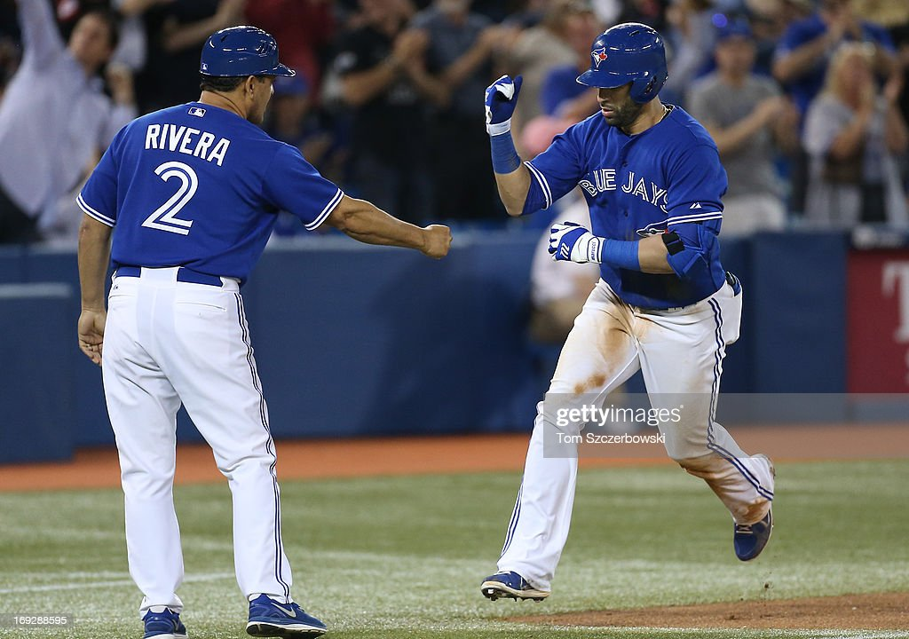 Jose Bautista #19 of the Toronto Blue Jays is congratulated by third base coach Luis Rivera #2 after hitting a game-tying solo home run in the ninth inning during MLB game action against the Tampa Bay Rays on May 22, 2013 at Rogers Centre in Toronto, Ontario, Canada.