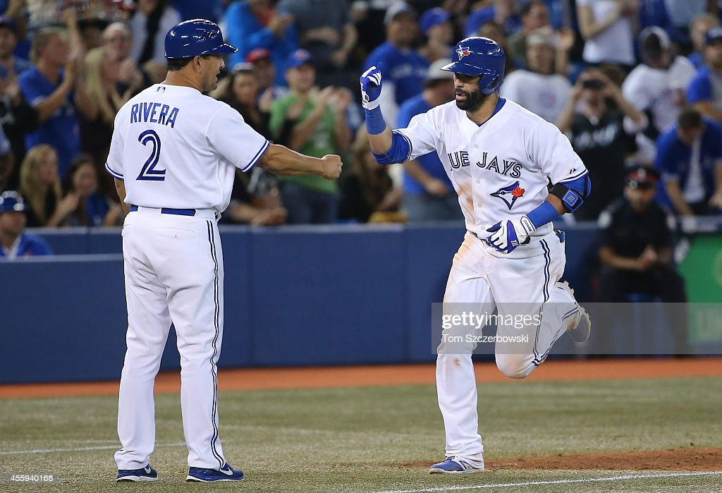 Jose Bautista #19 of the Toronto Blue Jays is congratulated by third base coach Luis Rivera #2 after hitting a solo home run in the fifth inning during MLB game action against the Seattle Mariners on September 22, 2014 at Rogers Centre in Toronto, Ontario, Canada.