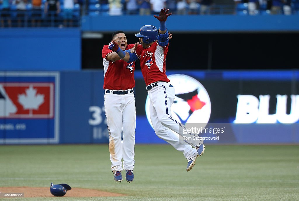 Jose Bautista #19 of the Toronto Blue Jays is congratulated on his game-winning hit by <a gi-track='captionPersonalityLinkClicked' href=/galleries/search?phrase=Melky+Cabrera&family=editorial&specificpeople=453444 ng-click='$event.stopPropagation()'>Melky Cabrera</a> #53 in the ninteenth inning during MLB game action against the Detroit Tigers on August 10, 2014 at Rogers Centre in Toronto, Ontario, Canada.