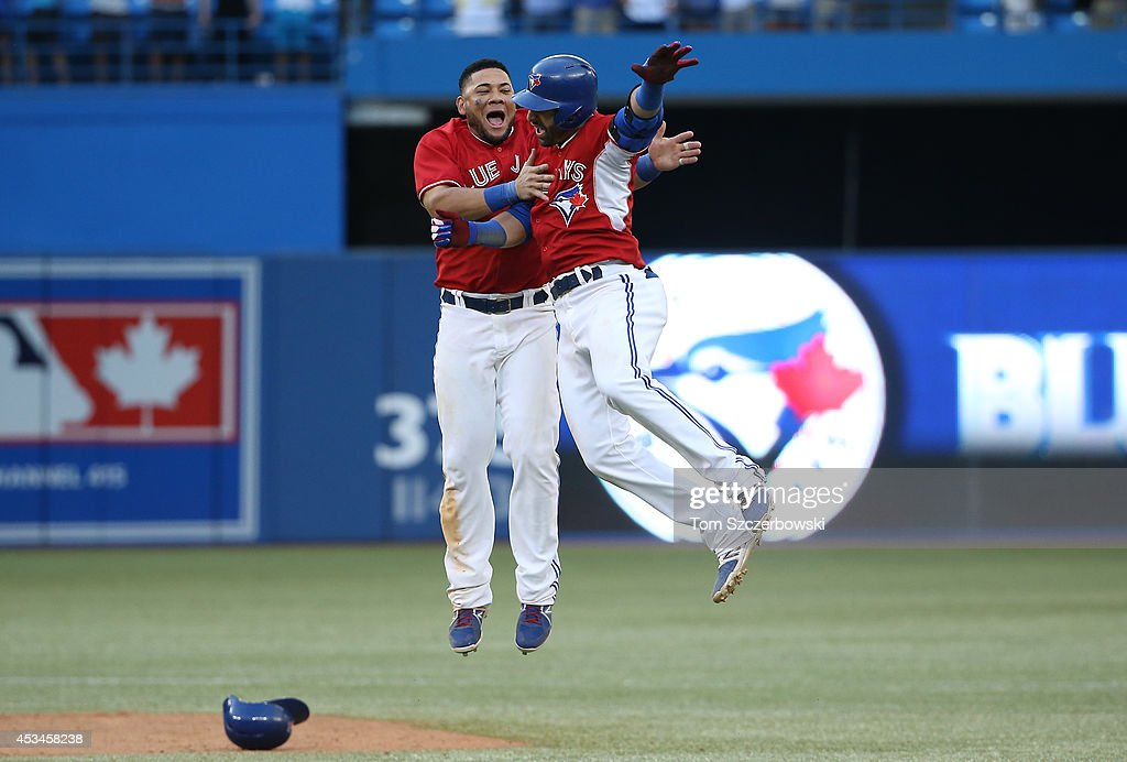 Jose Bautista #19 of the Toronto Blue Jays is congratulated on his game-winning hit by Melky Cabrera #53 in the ninteenth inning during MLB game action against the Detroit Tigers on August 10, 2014 at Rogers Centre in Toronto, Ontario, Canada.
