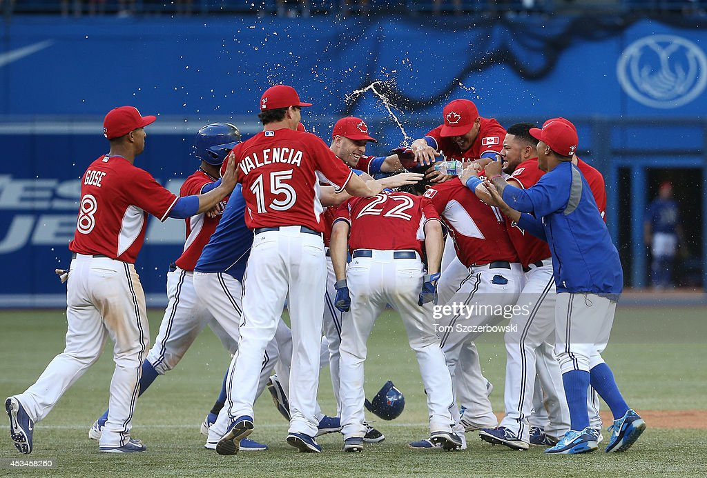Jose Bautista #19 of the Toronto Blue Jays is congratulated on his game-winning hit by teammates in the ninteenth inning during MLB game action against the Detroit Tigers on August 10, 2014 at Rogers Centre in Toronto, Ontario, Canada.