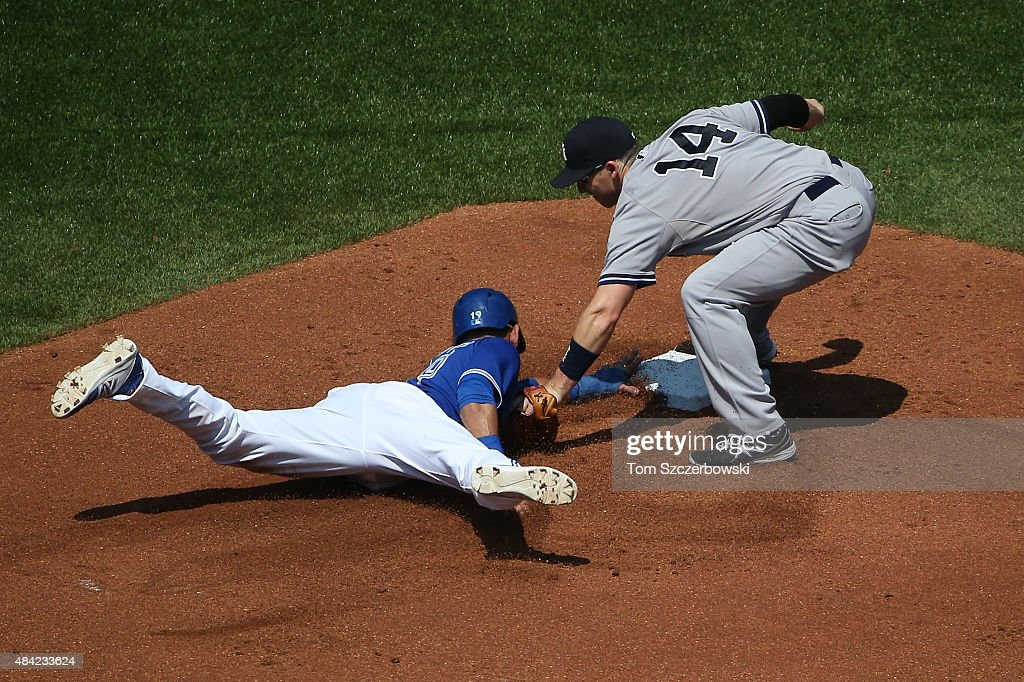 Jose Bautista #19 of the Toronto Blue Jays is picked off second base in the first inning during MLB game action as Stephen Drew #14 of the New York Yankees makes the tag on August 16, 2015 at Rogers Centre in Toronto, Ontario, Canada.