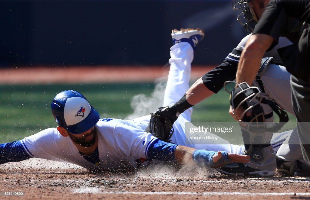 Jose Bautista #19 of the Toronto Blue Jays is tagged out at home plate by Austin Romine #27 of the New York Yankees in the fourth inning during MLB game action at Rogers Centre on September 24, 2017 in Toronto, Canada.