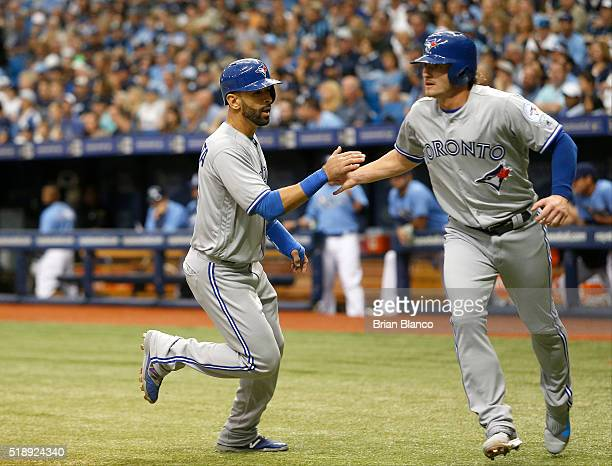 Jose Bautista of the Toronto Blue Jays left and teammate Josh Donaldson score off of a 2run single by Edwin Encarnacion during the first inning of a...
