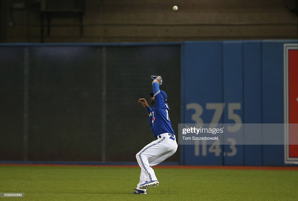 Jose Bautista of the Toronto Blue Jays misplays a bloop hit leading to two runs scoring on the play in the fifth inning during MLB game action...