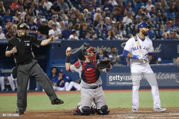 Jose Bautista of the Toronto Blue Jays reacts as he is called out on strikes by home plate umpire Sean Barber for his third strikeout of the game in...