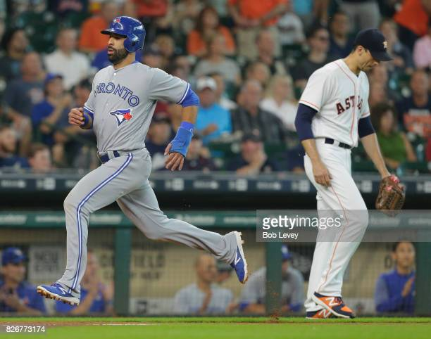 Jose Bautista of the Toronto Blue Jays scores in the first inning as he passes Charlie Morton of the Houston Astros at Minute Maid Park on August 5...