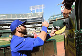 Jose Bautista of the Toronto Blue Jays signs autographs for fans prior to his game against the Oakland Athletics at Oco Coliseum on July 3 2014 in...