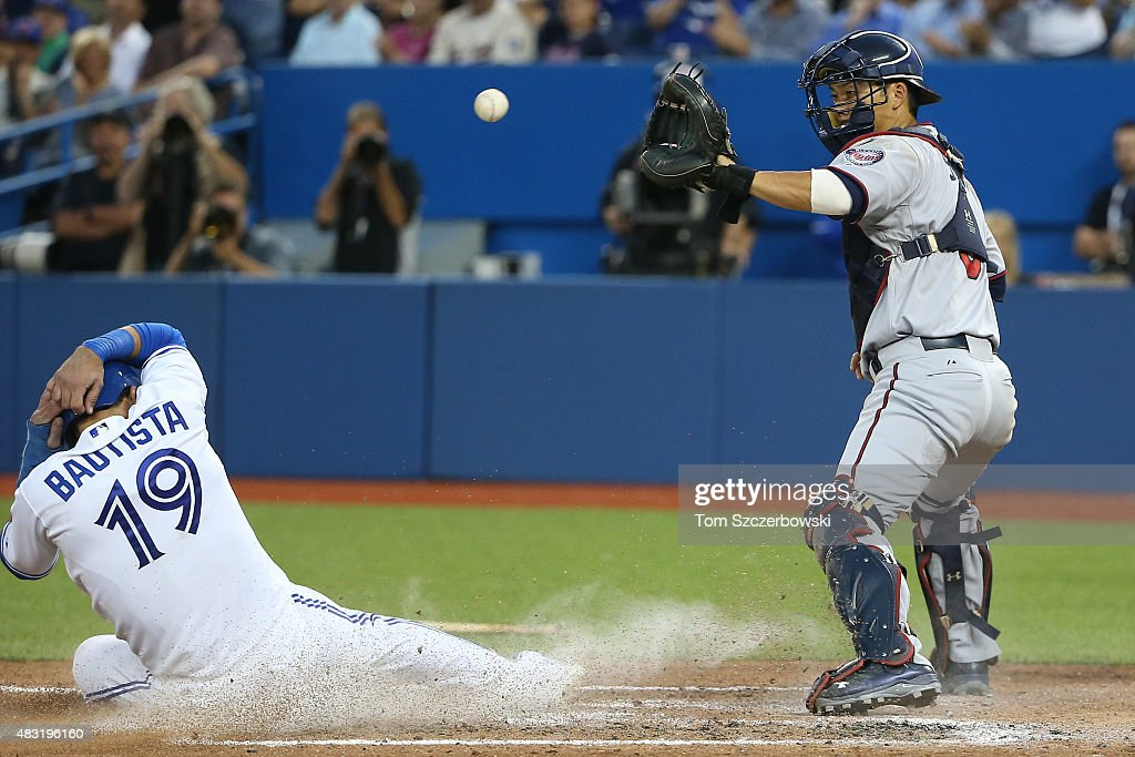 Jose Bautista of the Toronto Blue Jays slides home safely to score a run in the fifth inning during MLB game action as Kurt Suzuki of the Minnesota...