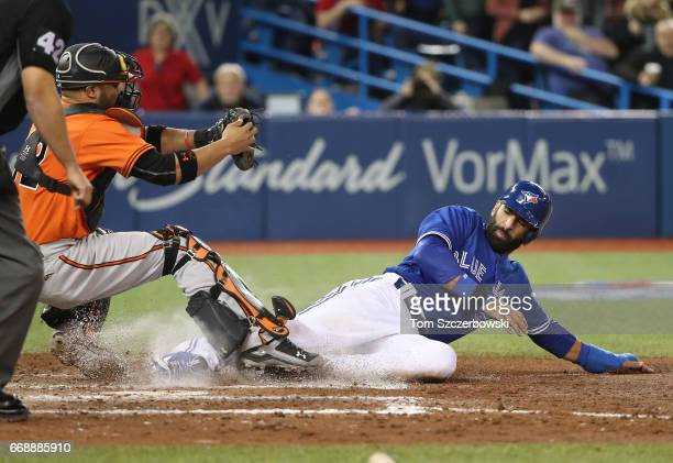 Jose Bautista of the Toronto Blue Jays slides home safely to score a run in the seventh inning during MLB game action as Welington Castillo of the...