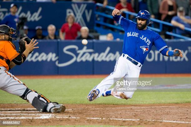 TORONTO ON APRIL 15 Jose Bautista of the Toronto Blue Jays slides into Orioles catcher Welington Castillo to score the games first run on an RBI by...