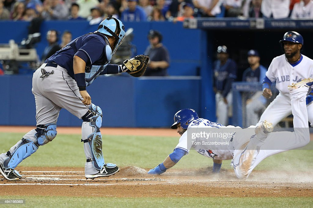 Jose Bautista #19 of the Toronto Blue Jays slides safely into home plate to score a run in the first inning during MLB game action as Jose Molina #28 of the Tampa Bay Rays attempts to tag him on May 28, 2014 at Rogers Centre in Toronto, Ontario, Canada.