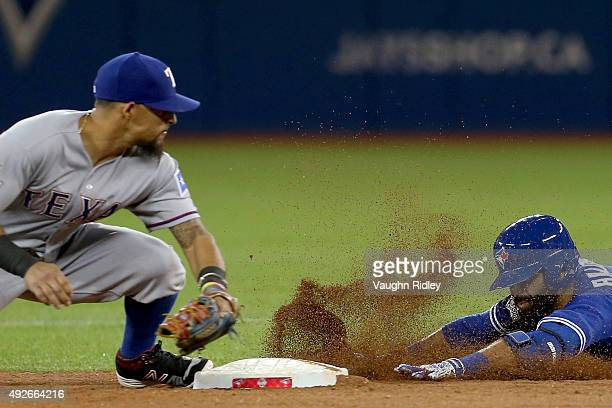 Jose Bautista of the Toronto Blue Jays slides safely into second base ahead of the tag by Rougned Odor of the Texas Rangers as Bautista gets a RBI...