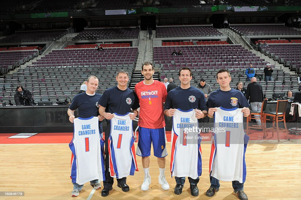 Jose Calderon #8 of the Detroit Pistons takes a picture with honored firefighters that went to New York to help with hurricane sandy relief efforts before the game against the Brooklyn Nets on February 6, 2013 at The Palace of Auburn Hills in Auburn Hills, Michigan.