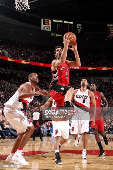 Jose Calderon of the Toronto Raptors drives to the basket for a layup against Marcus Camby and Juwan Howard of the Portland Trail Blazers during the...