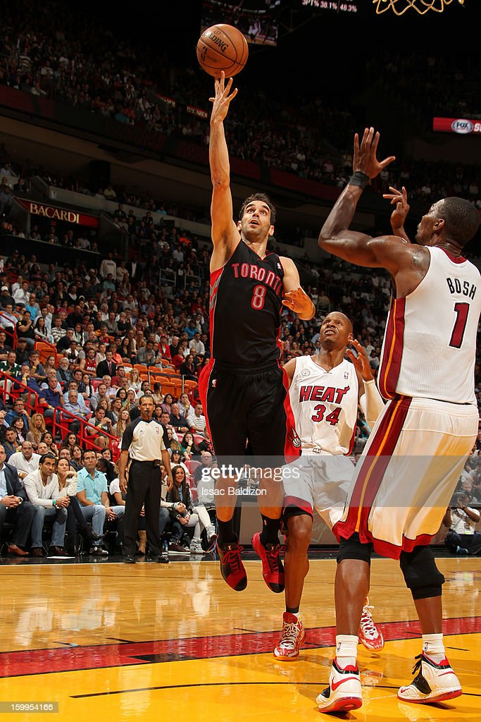 Jose Calderon #8 of the Toronto Raptors shoots against Chris Bosh #1 of the Miami Heat on January 23, 2013 at American Airlines Arena in Miami, Florida.