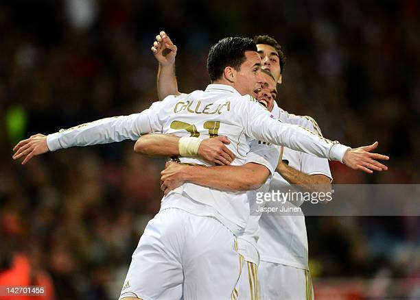 Jose Callejon of Real Madrid celebrates scoring with his teammates Pepe and Alvaro Arbeloa during the La Liga match between Club Atletico de Madrid...