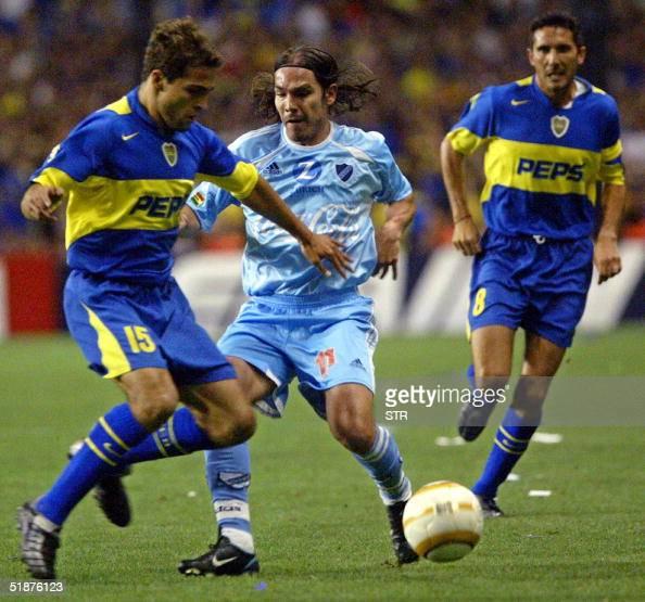 Jose Calvo of Boca Juniors of Argentina and Ruben Tufino of Bolivar de La Paz Bolivia vie for the ball while Diego Cagna looks on during the Copa...