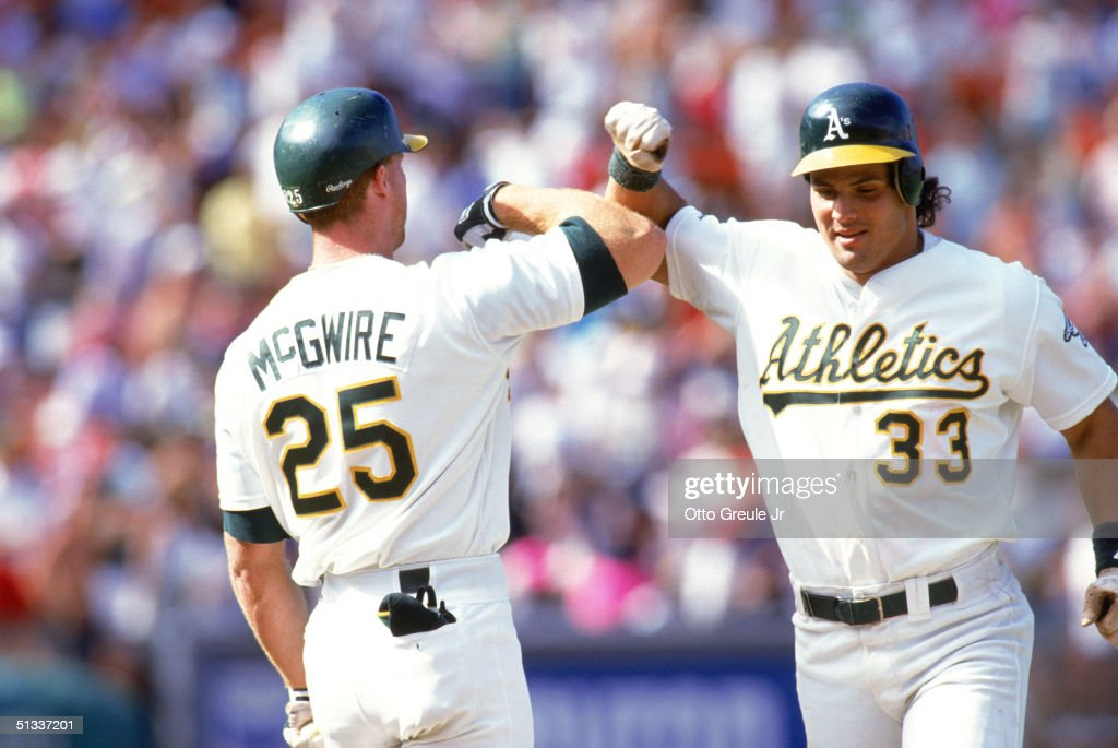 Jose Canseco #33 and Mark McGwire #25 of the Oakland Athletics celebrate during a 1990 MLB season game at Oakland-Alameda County Coliseum in Oakland, California.