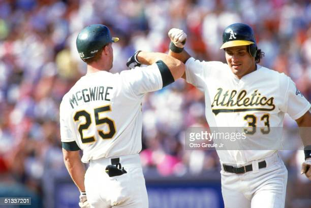 Jose Canseco and Mark McGwire of the Oakland Athletics celebrate during a 1990 MLB season game at OaklandAlameda County Coliseum in Oakland California
