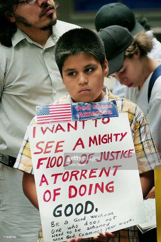 Jose Carlos Romero, 10, holds a sign showing support for employees of IFCO Systems during a press conference outside the building which houses the immigration court July 27, 2006 in Chicago, Illinois. Romero's father was among 26 illegal immigrants arrested in April in Chicago during a nationwide sweep of undocumented workers at IFCO Systems. He faces a deportation hearing on July 31.