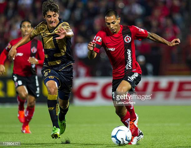 Jose Carlos Van Rankin of Pumas fights for the ball with Edgar Castillo of Xolos during a match between Tijuana and Pumas as part of Apertura 2013...