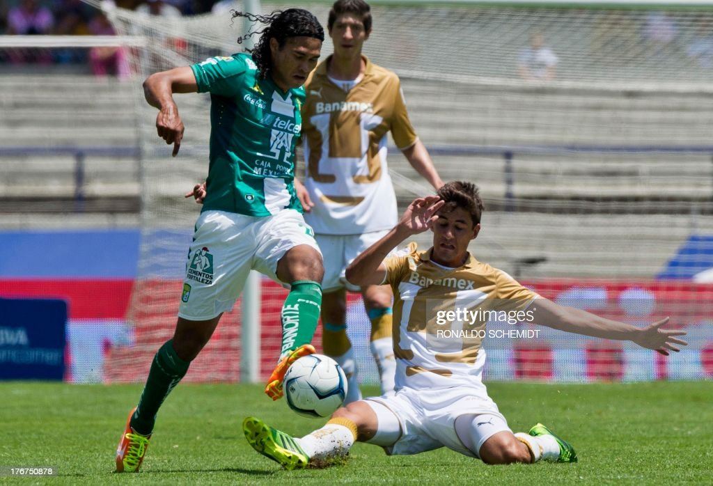 Jose Carlos Van Rankin (R) of Pumas vies for the ball with Carlos Pena (L) of Leon, during their 2013 Mexican Apertura tournament match in Mexico City, on August 18, 2013.