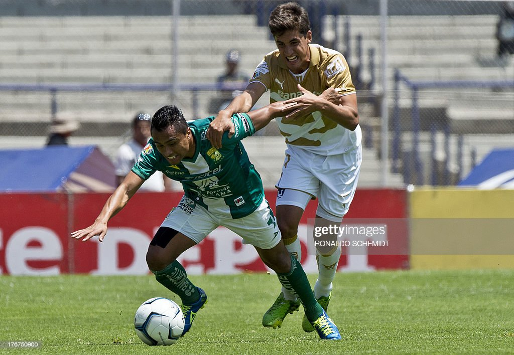 Jose Carlos Van Rankin (R) of Pumas vies for the ball with Edwin Hernandez (L) of Leon, during their 2013 Mexican Apertura tournament match in Mexico City, on August 18, 2013.