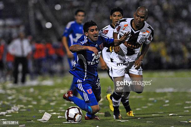 Jose Contreras of Universidad de Chile is fouled by Edgar Gonzalez of Peruvian Alianza Lima during their Copa Libertadores football match at Matute...