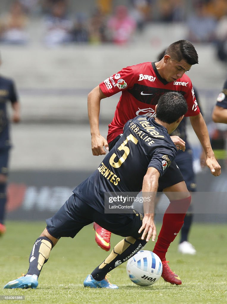 Jose Corona of Xolos Tijuana figths for the ball with Luis Fuentes of Pumas UNAM during a match between Pumas UNAM and Xolos Tijuana as part of 6th round Apertura 2014 Liga MX at Olimpic Stadium on August 24, 2014 in Mexico City, Mexico.