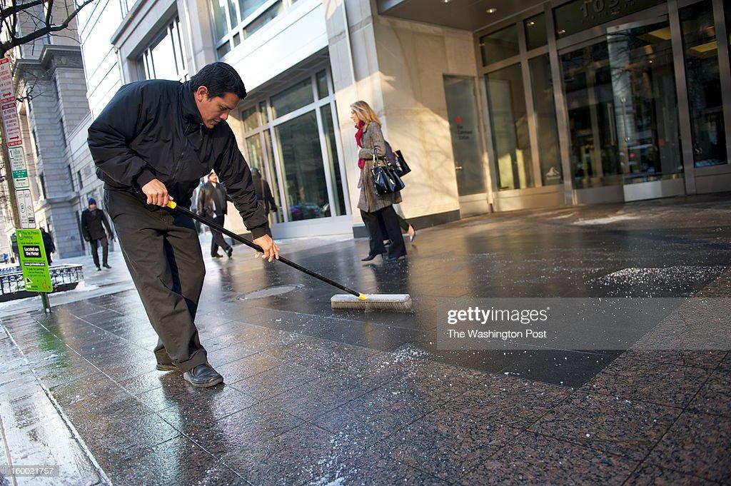 Jose Cruz from El Salvador sweeps salt from a sidewalk on 15th street, NW.