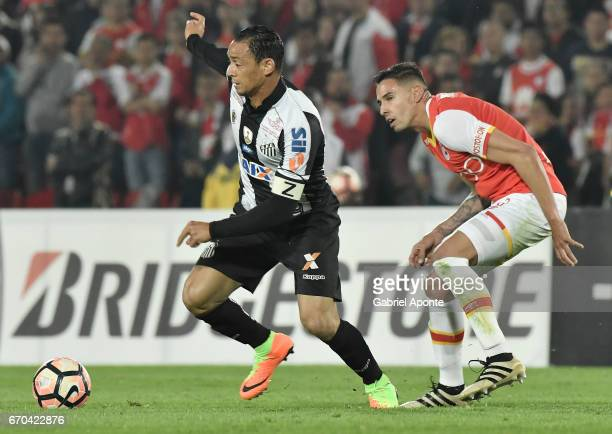 Jose David Moya of Santa Fe struggles for the ball with Ricardo Oliveira of Santos during a group stage match between Independiente Santa Fe v Santos...