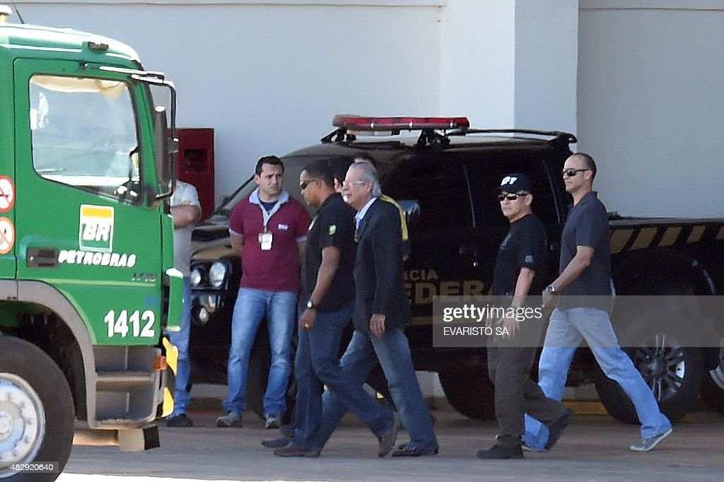 Jose Dirceu (C-grey hair), former Chief of Staff during Lula da Silva's government, is accompanied by polices to board a flight to Curitiba where he will appear before an inquiry commission investigating the scandal of corruption in state oil giant Petrobras, at Brasilia's airport on August 4, 2015. Dirceu was arrested Monday at home in Brasilia where he was serving a house arrest sentence after being convicted of involvement in the case of corruption known as Mensalao.
