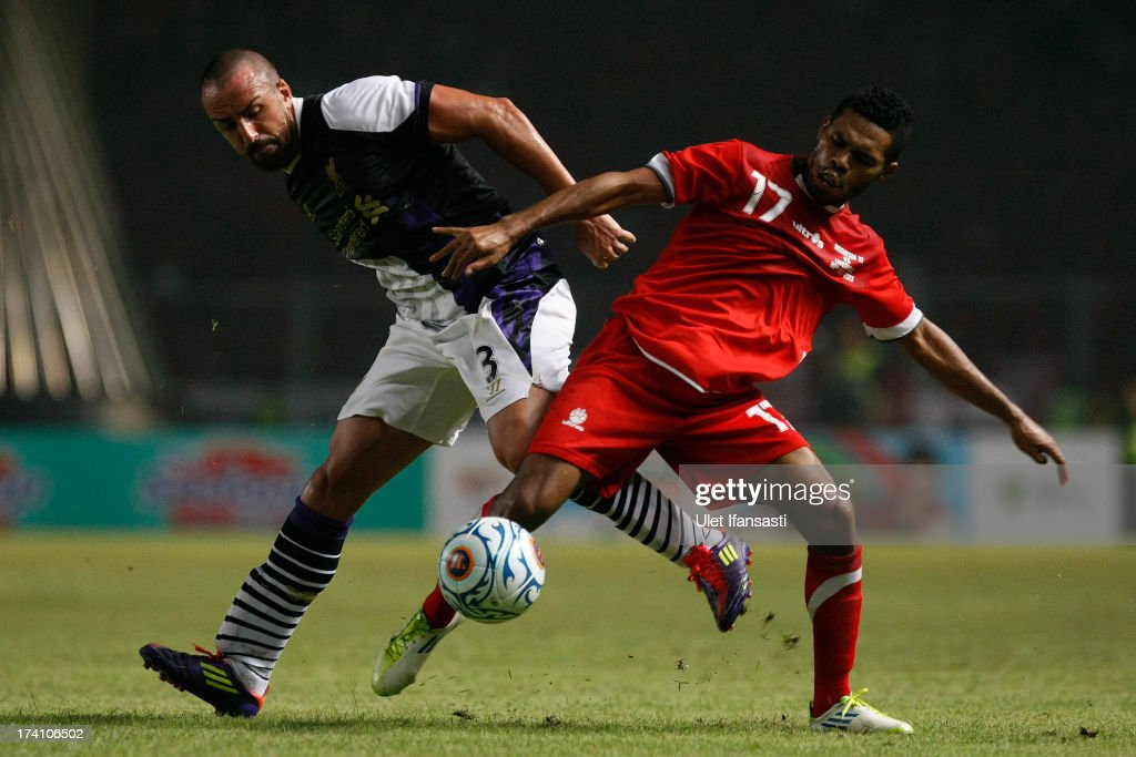 Jose Enrique of Liverpool battles for the ball with Yustinus Pae of Indonesia XI during the match between the Indonesia XI and Liverpool FC on July 20, 2013 in Jakarta, Indonesia.