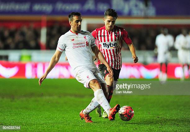 Jose Enrique of Liverpool beats Tom Nichols of Exeter City to the ball during the Emirates FA Cup third round match between Exeter City and Liverpool...