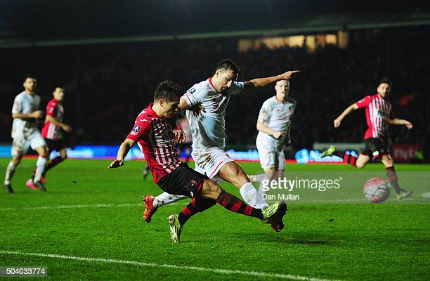 Jose Enrique of Liverpool challenges Tom Nichols of Exeter City as he shoots during the Emirates FA Cup third round match between Exeter City and...