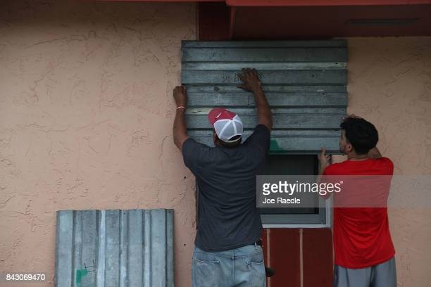 Jose Escobar and his son Jose Escobar jr puts up shutters as they prepare for Hurricane Irma on September 5 2017 in Homestead Florida A state of...