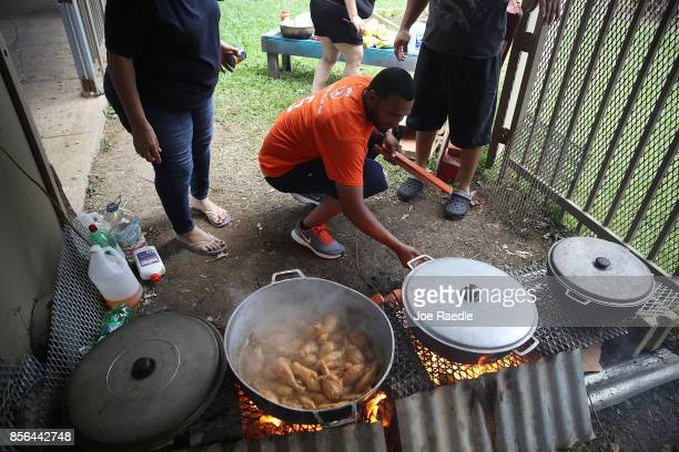 Jose Estrada helps cook a communal pot of food at the Torres de Francia complex as they deal with the aftermath of Hurricane Maria on October 1 2017...