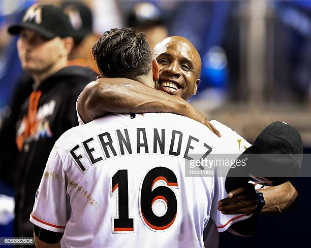 Jose Fernandez of the Miami Marlins celebrates in the dugout with hitting coach Barry Bonds during the game against the Washington Nationals at...