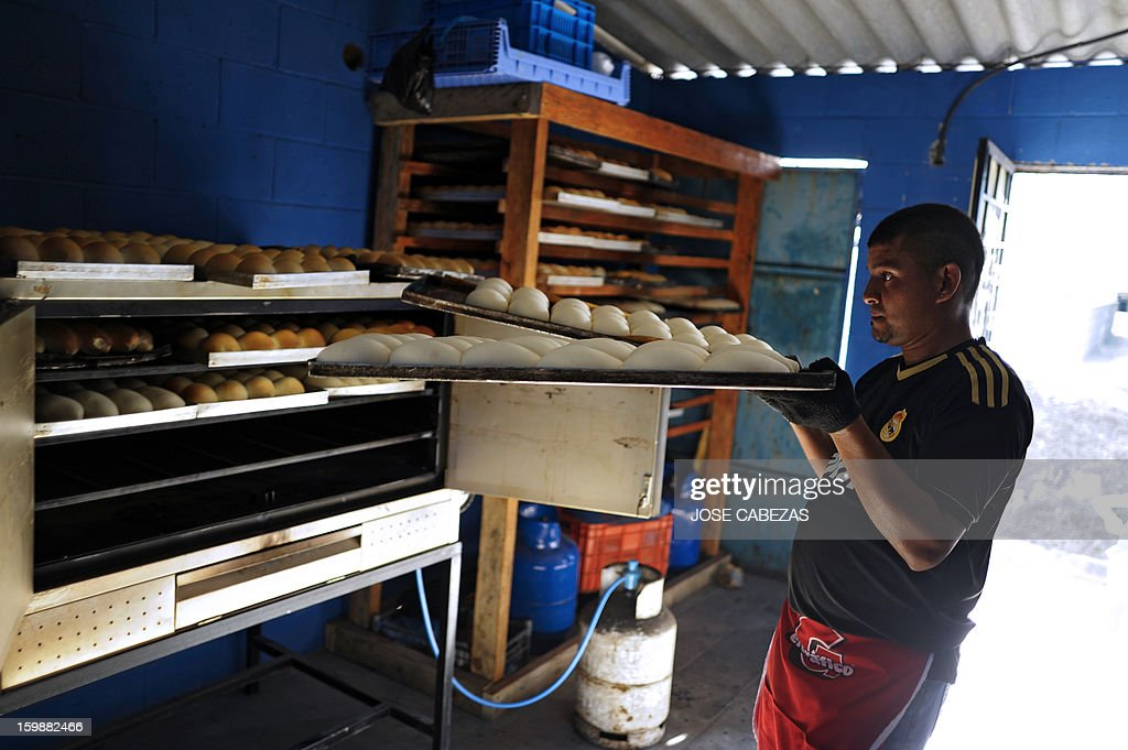 Jose Galdamez, of the 18th street gang, puts dough in the oven at a bakery operated by gang members as a part of a rehabilitation program in San Bartolo neigbourhood, in Ilopango, a suburb of San Salvador on January 21, 2012. Gang leaders started the second phase of the gang truce to reduce crime in El Salvador. AFP PHOTO/ Jose CABEZAS