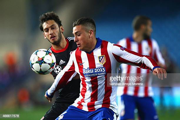 Jose Gimenez of Atletico Madrid and Hakan Calhanoglu of Bayer Leverkusen compete for the ball during the UEFA Champions League round of 16 match...