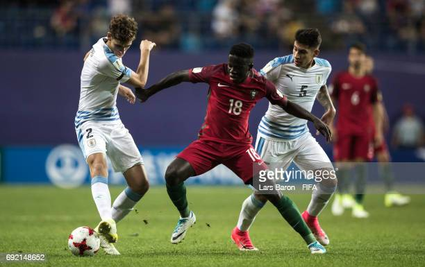 Jose Gomes of Portugal is challenged by Santiago Bueno of Uruguay and Mathias Olivera of Uruguay during the FIFA U20 World Cup Korea Republic 2017...