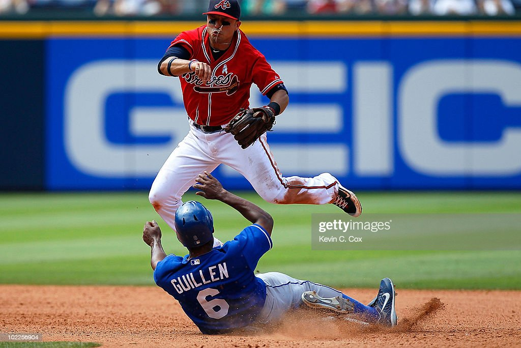 <a gi-track='captionPersonalityLinkClicked' href=/galleries/search?phrase=Jose+Guillen&family=editorial&specificpeople=202215 ng-click='$event.stopPropagation()'>Jose Guillen</a> #6 of the Kansas City Royals slides into <a gi-track='captionPersonalityLinkClicked' href=/galleries/search?phrase=Martin+Prado&family=editorial&specificpeople=620159 ng-click='$event.stopPropagation()'>Martin Prado</a> #14 of the Atlanta Braves at second base to break up a double play at Turner Field on June 20, 2010 in Atlanta, Georgia.