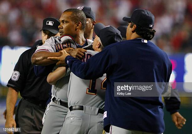 Jose Guillen of the Washington Nationals is restrained by bench coach Eddie Rodriguez and Vinny Castilla after an argument with Los Angeles Angels of...