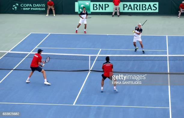 Jose Hernandez of the Dominican Republic returns the ball next to teammate Roberto Cid during the Davis Cup first round double tennis match against...