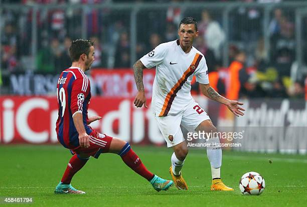 Jose Holebas of AS Roma beats Mario Goetze of Bayern Muenchen to the ball during the UEFA Champions League Group E match between FC Bayern Munchen...